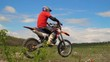 Professional motor biker jumping over in slow motion on a motocross track.