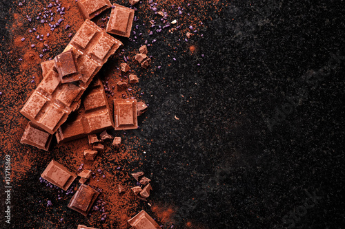Canvas Print Broken chocolate pieces and cocoa powder on marble.