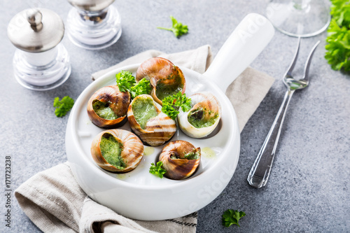 Bourgogne Escargot Snails with garlic herbs butter in white pan on light gray background. Healthy food concept.