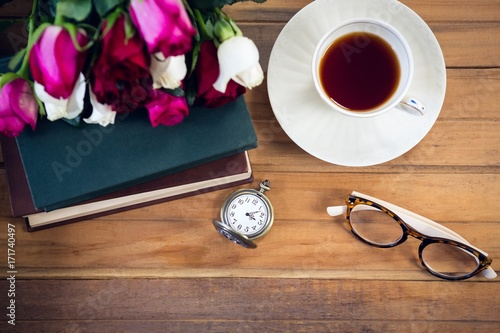 Overhead view of eyeglasses by stopwatch and tea with books