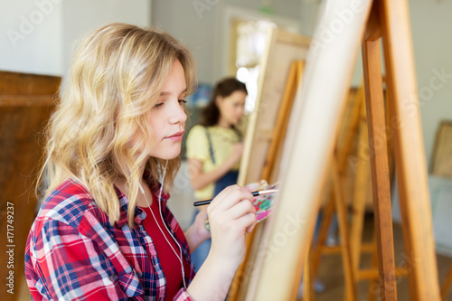 Photo  student girl with easel painting at art school