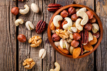 Nuts Mixed In A Wooden Plate.Assortment, Walnuts,Pecan,Almonds,Hazelnuts,Cashews,Pistachios.Concept Of Healthy Eating.Vegetarian.selective Focus.