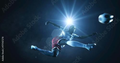 Fotografia  Soccer player kicks the ball on the soccer stadium