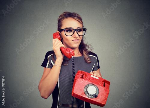 Fotografie, Tablou  Grumpy displeased young woman having unpleasant phone conversation