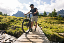 Young Adult Active Man On Wooden Little Bridge On Mountain Wearing Bike Helmet Looking At River Holding Electric Bike In Sunny Summer Day Outdoor.