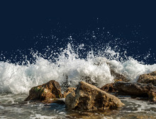 Splashing Sea Water On Rocks Isolated On A Dark Blue Background