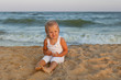 Cute baby girl sitting on the seashore