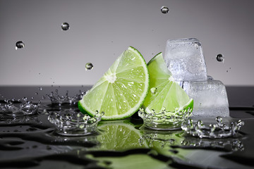Fototapeta Lime slices with water drops and ice cubes