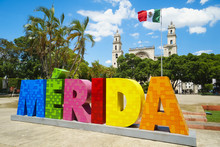 MERIDA, MEXICO - MAY 23, 2017: Colorful Sign Merida With Mexican Flag And Cathedral On A Street In Sunny Summer Day