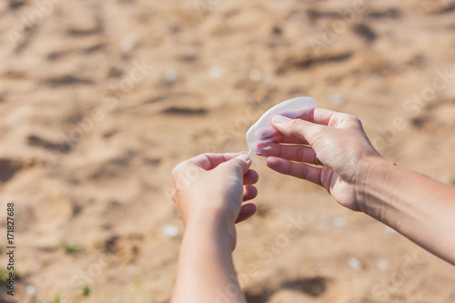 Woman holds a white feather of a seagull in hand Wallpaper Mural
