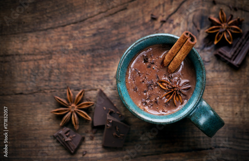 Spoed Foto op Canvas Chocolade Hot chocolate in a cup with a cinnamon stick, anise star and dark chocolate flakes on rustic wooden background with an empty tag. Overhead view with copy space for your text