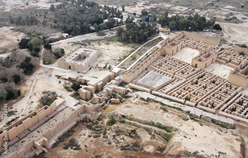 Fotobehang Rudnes Restored ruins of the South palace of Nebuchadnezzar in ancient Babylon, Iraq on the right. Ruins of the North palace damaged by US occupation on the left. Beyond Processional Street is Ninmah temple.