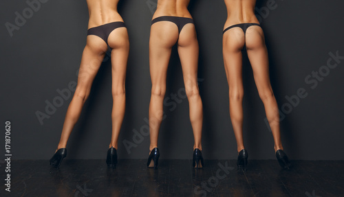 Valokuva  Three pairs of bare female legs leaning to the wall