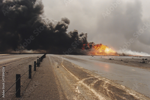 Photo  Road through oil well burning in field with oil slick, Kuwait