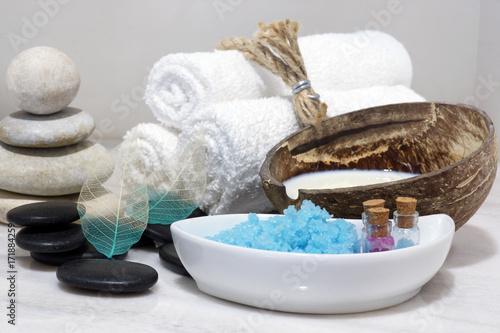 Zdjęcie XXL Zestaw do zabiegów Spa z mlekiem kokosowym, gorącymi kamieniami i niebieską solą do kąpieli znajduje się na białym marmurowym blacie.
