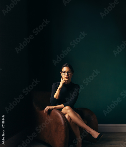Portrait of pensive young woman sitting on chaise longue