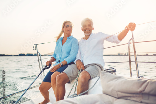 Smiling couple sailing their boat together on a sunny afternoon