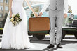canvas print picture - Happy wedding couple with suitcase and car outdoors