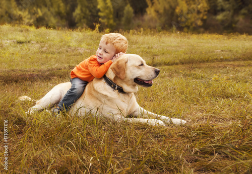 Little boy sits astride dog on walk in park. Copyspace Canvas Print