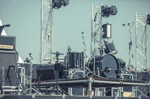 Plakat Nowoczesny zestaw perkusyjny na scenie przygotowany do grania w jasnoniebieskim świetle. instalacja muzyczna z bębnami stojącymi na zewnątrz sceny przed koncertem. Zestaw perkusyjny na scenie w kolorze reflektorów