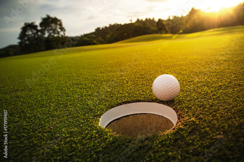 Deurstickers Golf selective focus. white golf ball near hole on green grass good for background with sunlight and lens flare effect