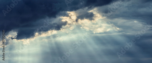 Foto Beautiful dark storm cloudy sky with rays of the sun breaking through the clouds