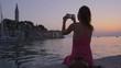 Woman taking selfie on a sunset in a Rovinj, Croatia