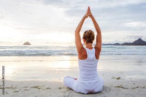 Stampe Caucasian woman practicing yoga at seashore of tropic ocean
