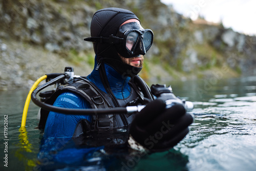 Keuken foto achterwand Duiken Male diver in wetsuit checking equipments before immerse