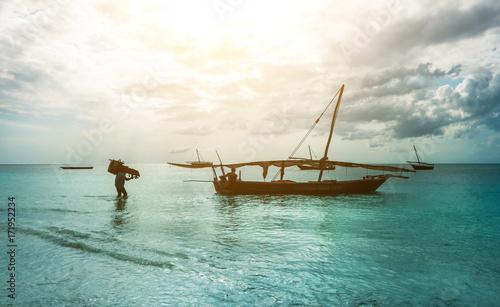 Poster Zanzibar Old rustic fishing boat sitting in the ocean, calm and still turquoise waters, zanzibar