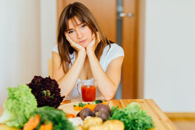 Brunette Woman Looking On Fresh Detox Juice, Smoothie For Breakfast. Closeup Of Beautiful Sad, Thoughtful Girl With Vegetables At Kitchen Table. Diet Concept.