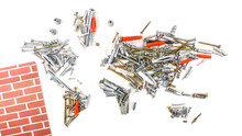 Map Of The World Made Of Screws, Fasteners And Other Mechanical Tools With Small Part Of Red Wall