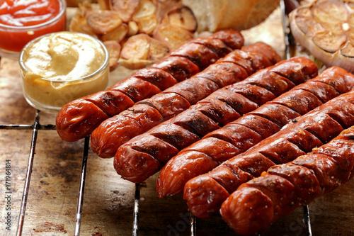 Plakat Grillowane kiełbaski z sosem ketchup i musztardą na ruszcie metalowym