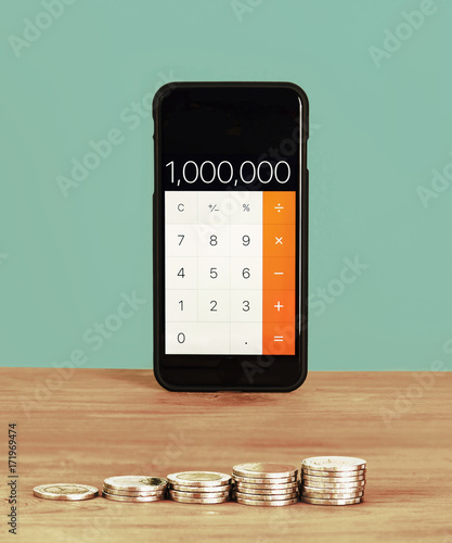 Smartphone used as calculator, Set a goal to save one million and many coin on wooden table, Saving money concept, Vintage color. - 171969474