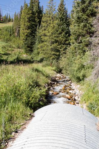 Fotografia, Obraz  Stream through a metal corrugated culvert in Colorado