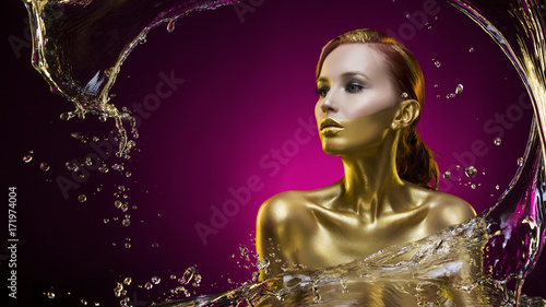 beautiful topless gilded young girl covered with water splash on a violet background
