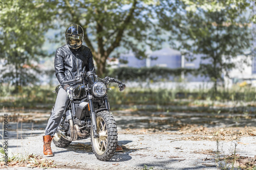 Motorcycle rider on custom made scrambler style cafe racer in the park Wallpaper Mural
