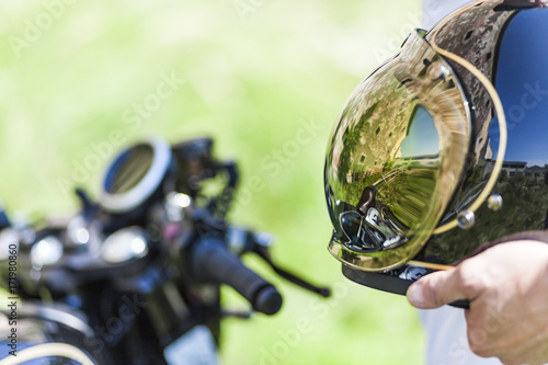 Reflection of custom made scrambler style cafe racer in the helmet Fototapeta
