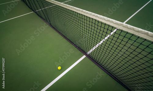 Plakat piłka tenisowa w pobliżu sieci na twardym boisku