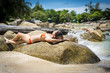 Pretty woman lying at rock