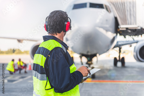 Stampa su Tela Male worker controlling aircraft and writing information