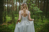 Fototapeta Las - Bride in white wedding dress walking in forest. Fashion and nature background.