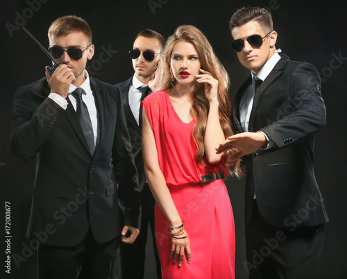 Fotografía  Famous celebrity with bodyguards on dark background