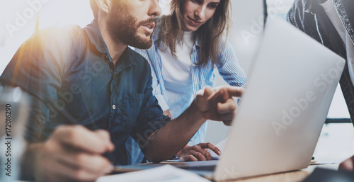 Group of coworkers sitting at the wooden table and working together on new startup project in modern loft office.Horizontal.Blurred background.Cropped.
