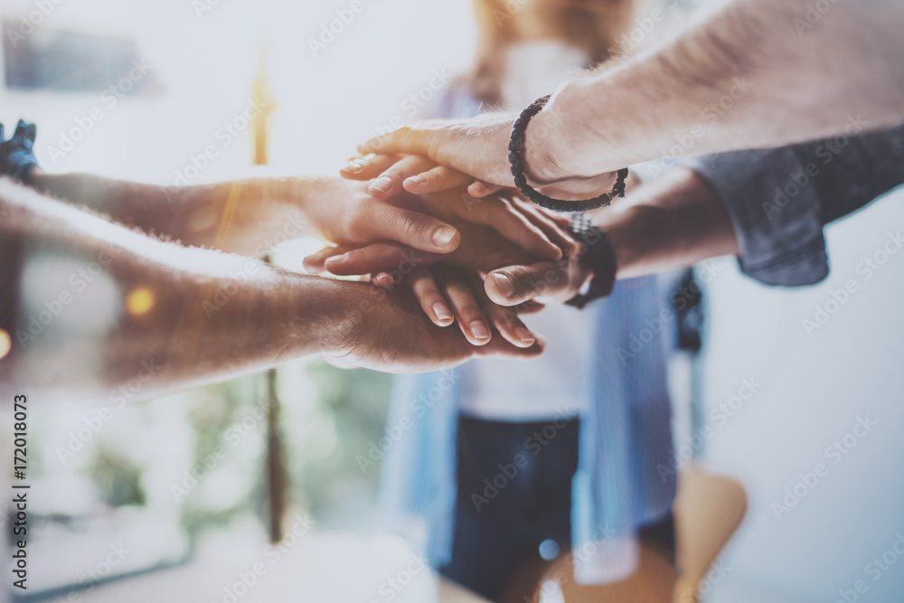 Fototapeta Teamwork business concept.Close up view of group of three coworkers join hand together during their meeting. Horizontal.Blurred background.