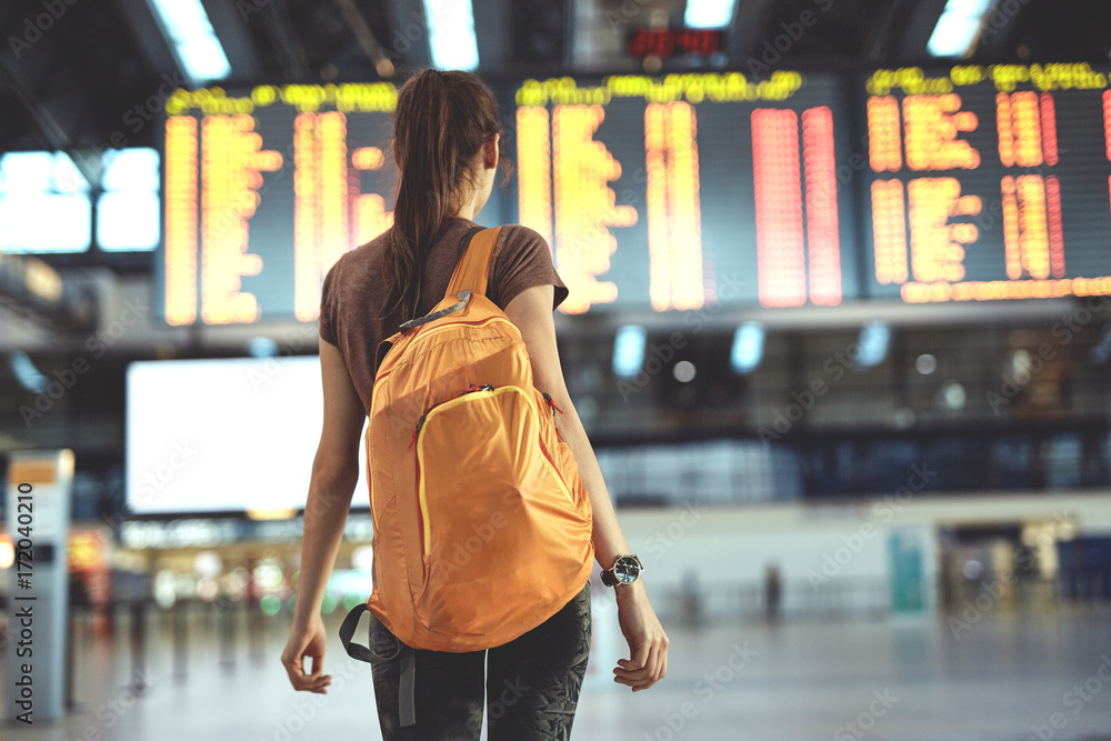 Fototapeta Young woman with small backpack as a hand luggage in international airport looking at the flight information board, checking her flight