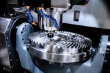 A modern CNC milling machine makes a large cogwheel.