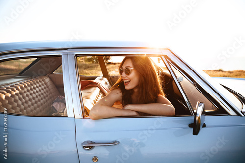 Fotografie, Tablou  Side view of smiling woman in sunglasses sitting inside car