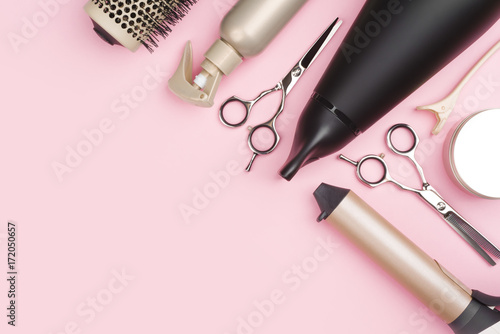 Professional hairdressing tools on pink background with copy space