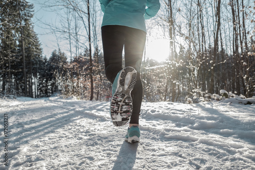 Cadres-photo bureau Glisse hiver Woman Running at snowly winter under sunlight.